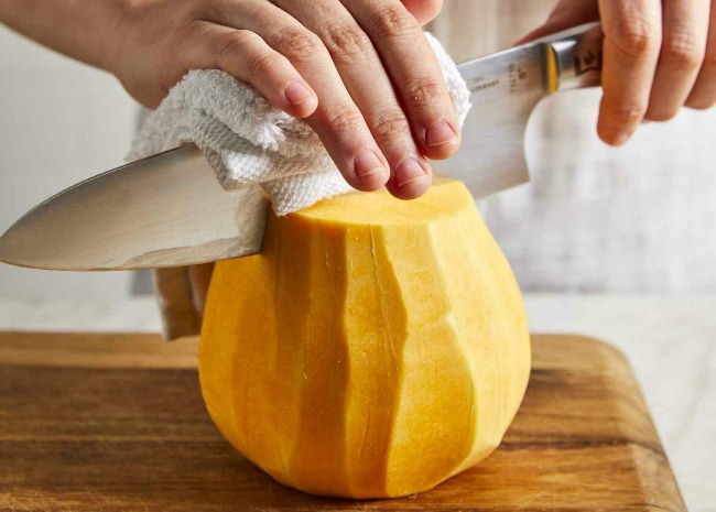 cutting a peeled butternut squash
