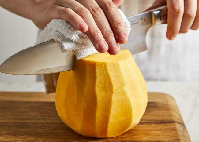 cutting up a peeled butternut squash